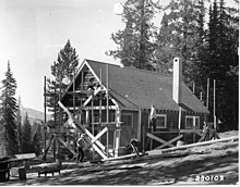Photo of men working to construct a cabin
