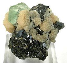 Associazione di galena (cristalli scuri), fluorite (cristallo verdognolo con lucentezza vitrea) e aggregati di piccoli cristalli biancastri di calcite