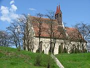 A stone church with a small tower on a hill
