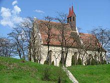 Une église en pierre avec une petite tour sur une colline