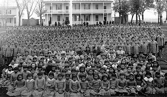 Native youth in front of Carlisle Indian Industrial School in Pennsylvania c. 1900 Carlisle pupils.jpg