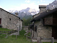 Two stone houses, with mountain in background