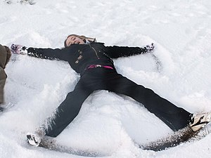 A child making a snow angel in shallow snow.