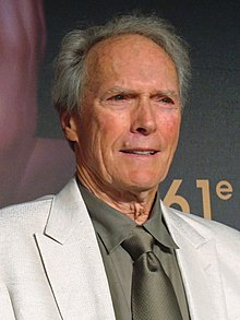 An older man is at the center of the image smiling and looking off to the right of the image. He is wearing a white jacket, and a tan shirt and tie. The number 61 can be seen behind him on a background wall.