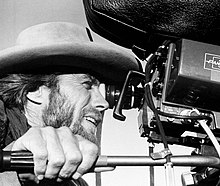 A man is seen looking into the viewfinder of a Panavision camera.