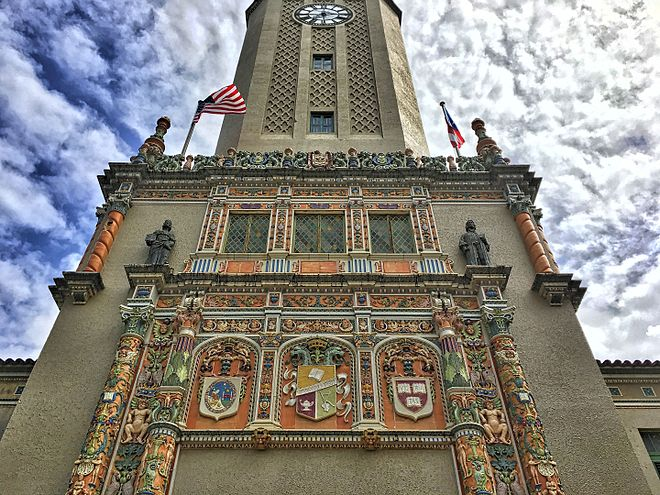 Tower at the University of Puerto Rico, showing (right) the emblem of Harvard University--the oldest in the United States--and (left) that of National University of San Marcos, Lima--the oldest in the Americas Clock Tower University of Puerto Rico-San Marcos-Harvard.jpg