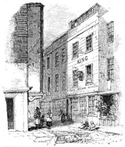 "A monochrome illustration of a narrow street, viewed from a corner, or intersection. A large three-storey building is visible on the right of the image. The ground floor has three windows, the first and second floors have two windows each. The roof appears to contain a row of windows, for a loft space. The word ""KING"" is written between the first and second floors, and a sign, ""Gas meter maker"" hangs above the ground floor windows."