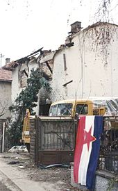 A blue-white-red Yugoslav flag, with the red Communist star in the middle, hangs on an iron fence outside the ruined shell of a house. A truck is partly visible parked in the driveway next to the building.