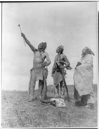 Crow Nation - The Oath Apsaroke by Edward S. Curtis depicting Crow men giving a symbolic oath with a bison meat offering on an arrow