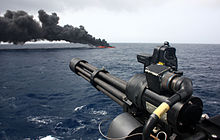 Photograph of a drug vessel burning in the background, with a ship-mounted minigun in the foreground.