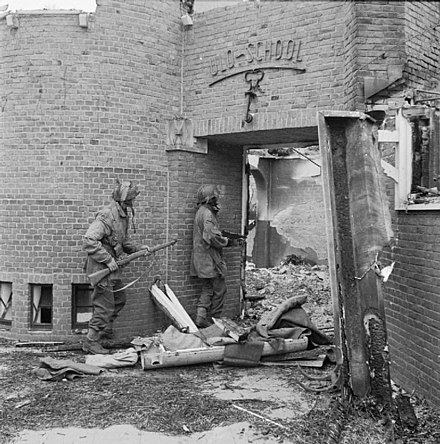 A Dutch school damaged by mortar fire, being searched for German snipers by Sergeant J. Whawell and Sergeant J. Turrell of the Glider Pilot Regiment. An empty CLE Canister lies open on the ground in the doorway of the school. 20 September 1944 Dutch school being searched for German snipers.jpg