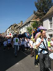 Eel day parade view down Fore Hill showing people in white Eel day tee-shirts walking towards the camera
