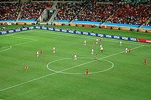 Photo d'un match de football entre une équipe jouant en blanc et l'autre en rouge vu depuis les tribunes