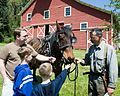 Farmer talking with people in front of farmer house with horse.jpg