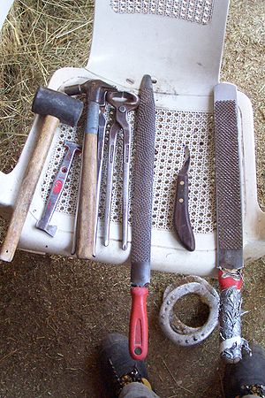 Farrier - Some farrier tools, including hammers,  nippers, rasps, and hoof knife, a set of custom-made corrective shoes are shown below the toolset