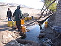 Fetching water from spring water channel (4361656507).jpg