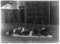 Five girls lying on mat in gymnasium in front of basketball scoreboard.png