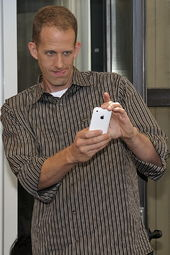 The portrait of a man holding a white telephone. He is wearing a striped brown shirt.