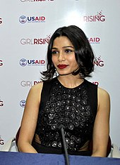 Freida Pinto is looking away from the camera.