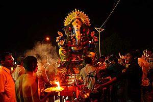 Sukhakarta Dukhaharta - A priest (left, bottom) performs aarti of Ganesha.