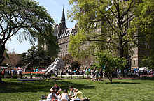 Many students mingle in the background while a group sit in the foreground on a grass lawn. The large stone clocktower is seen above the trees on the lawn.
