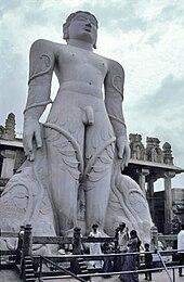Gigantesca statua in pietra grigia di uomo nudo con rampicanti che si arrampicano sulle gambe fino alle braccia