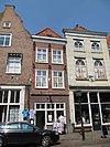 foto van Smal pand met schilddak en lijstgevel met fraai gesmede ankers; vensteromlijstingen; beneden winkel
