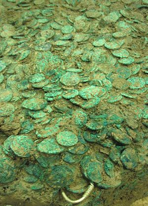 Grouville Hoard - The excavated hoard undergoing cleaning and investigation. Jewellery can be seen protruding from the mass of coins.