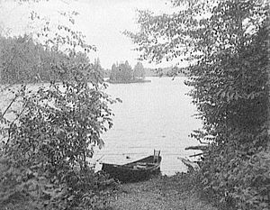 """Adirondack guideboat - Guideboat on Upper St. Regis Lake, showing the """"sport's"""" seat, in the stern (1900-1910)."""