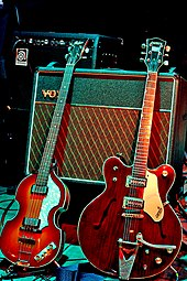 Two electric guitars, the light brown violin-shaped bass and the darker brown guitar, rest against the Vox amplifier.