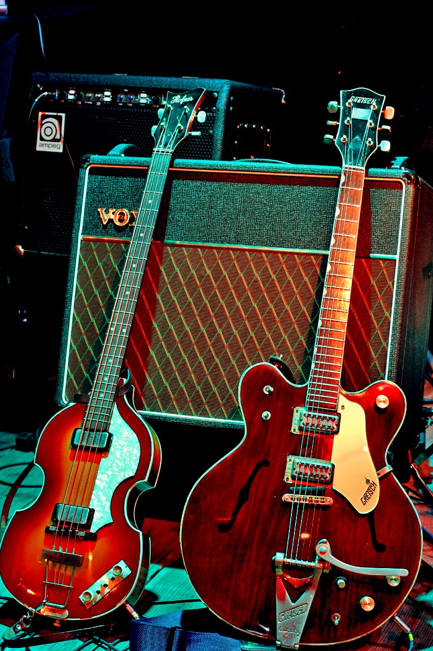 Two electric guitars, a light brown violin-shaped bass and a darker brown guitar, resting against a Vox amplifier