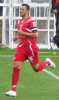 A man wearing a red football kit.