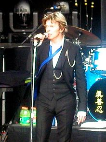 A male singer wearing a dark grey three-piece suit, white shirt and a blue undone tie, on stage singing while holding a microphone on a stand.