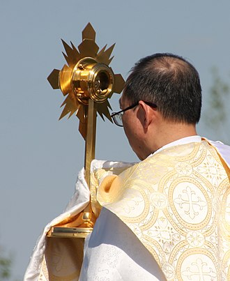 Monstrance - The Blessed Sacrament in a monstrance carried in a procession by a priest wearing a humeral veil