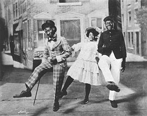 African-American musical theater - George Walker, Adah Overton Walker and Bert Williams dance the cakewalk in the first Broadway musical written and performed by African Americans, In Dahomey (1903).