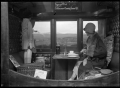 Interior of a railway carriage, showing several items of New Zealand Railways picnic equipment ATLIB 330290.png