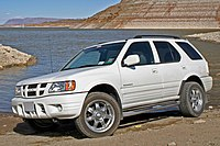 A white 2004 Isuzu Rodeo by a reservoir in the desert