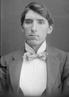 A black and white portrait photograph of a Caucasian man in his twenties wearing a suit and bowtie