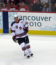 "An ice hockey player is skating on the ice. He is in a white jersey with the letters ""USA"" going diagonally across his jersey."