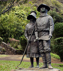 Photo displaying one male and one female bronze figure both wearing hats