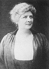 Zwart-wit, driekwart foto van een vrouw met opgestoken, grijzend haar, gekleed in een donkergekleurde jurk