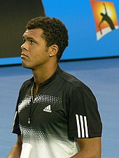 Tsonga in a white shirt lookinh away from the camera.