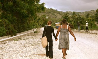 Jodi Shelton - Jodi Shelton walks hand-in-hand with a local woman on her last visit to Haiti with the BuildOn organization
