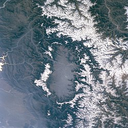 Kashmir valley seen from a satellite. Snow-capped peaks of the Pir Panjal Range (left in the image; southwest in compass) and the هیمالیا (right in image; northeast in compass) flank the valley