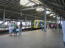 A relatively empty boarding platform with only a handful of people identified by a sign as that at Vito Cruz station. Pebbles line the tracks and sunlight comes in from spaces open to the outside and large open flaps in the dark warehouse-like roof.