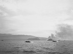 A harbor with a number of amphibious ships racing from battleships out to sea to the shore