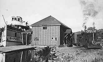 Huntsville and Lake of Bays Transportation Company - The SS Algonquin docks at North Portage station outside of Huntsville, Ontario. The two-locomotive train of the Huntsville and Lake of Bays Railway waits for passengers to board before leaving for South Station, a short distance away.