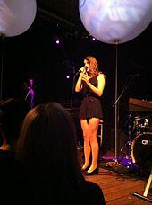 Une femme brune chante sur une scène devant une foule, vêtue d'une robe noire qui couvre au-dessus des genoux et de talons hauts noirs.  Un ballon bleu masque le coin supérieur droit.