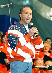 A middle-aged man wearing a jacket with an American flag design and blue jeans, singing into a microphone