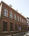 In Traditioneel-ambachtelijke stijl in opdracht van M.B. Ulens, overste van de Ursulinen gebouwde school.